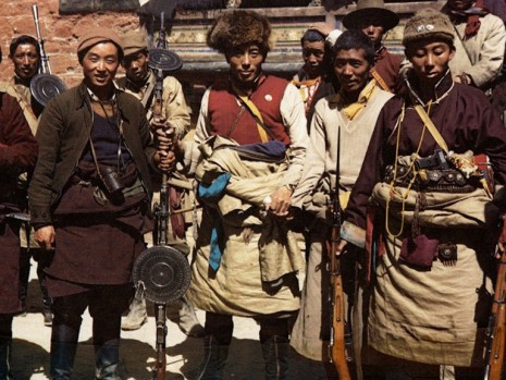 Ratuk Ngawang la at Tsetang. He is holding a captured Russian DP-28 light machine gun with circular pan magazine. Tibetans called it chikhang. To his right is the war photographer, Tsongon Jhanjup Jinpa.